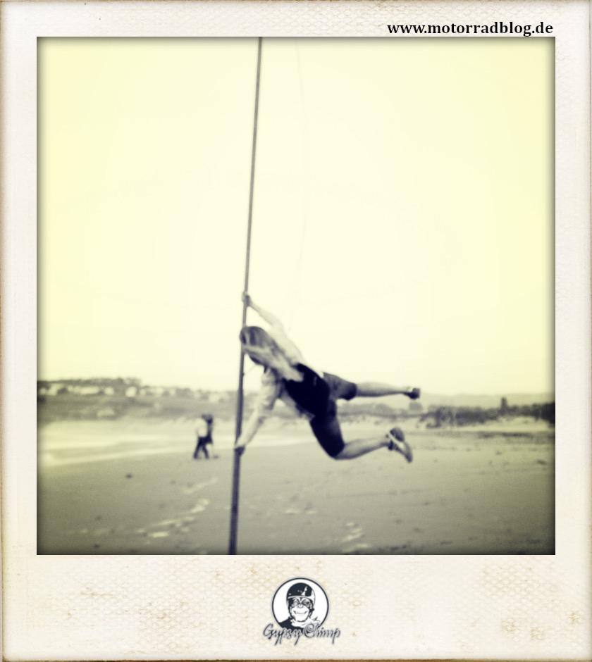 [Hier ist eigentlich ein Bild: Eine junge Frau, die am Strand an einem Stab emporspringt.]