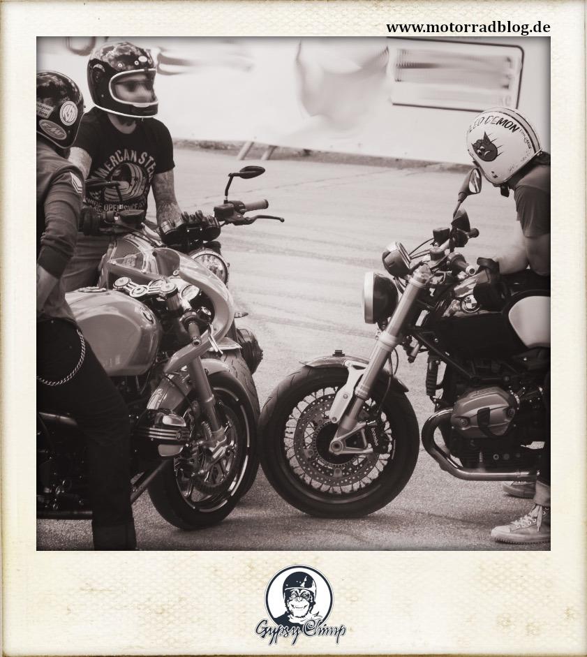 [Hier ist eigentlich ein Bild: Drei Motorräder von BMW, deren Vorderreifen sich berühren. Die Fahrer tragen T-Shirts und Helme im Vintage-Stil.]