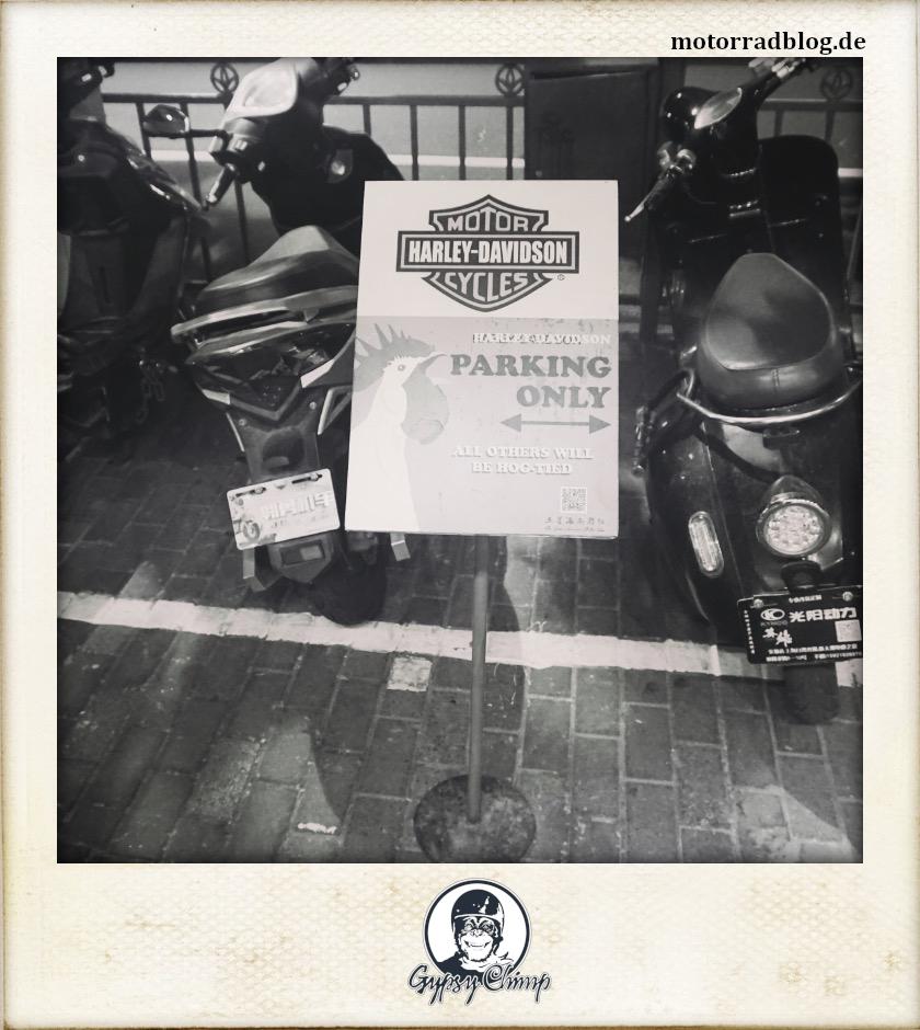 [Hier ist eigentlich ein Bild: Im Hintergrund drei parkende Motorroller mit chinesischem Nummernschild. Davor ein Schild, dass das Parken nur für Motorräder von Harley-Davidson erlaubt.]