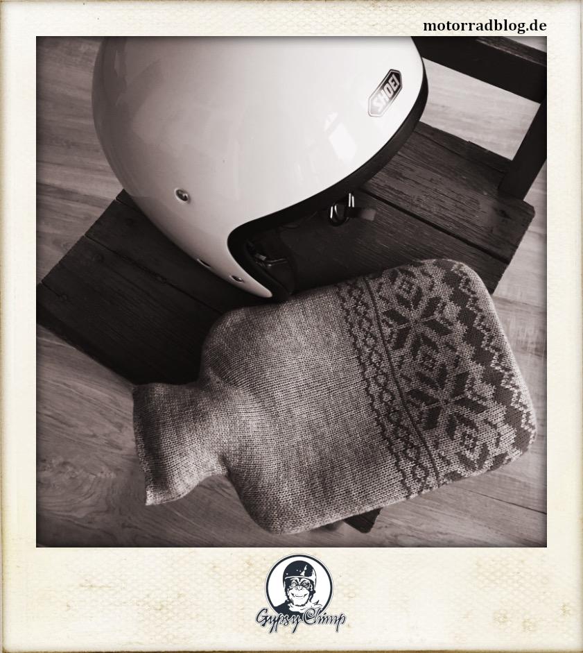 [Hier ist eigentlich ein Bild: Ein Motorradhelm und eine Wärmflasche, die auf einem Stuhl liegen.]